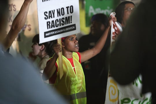 A protester holds signs outside a Donald Trump rally at the Santa Ana Star Center in Rio Rancho on Monday, Sept. 16, 2019.
