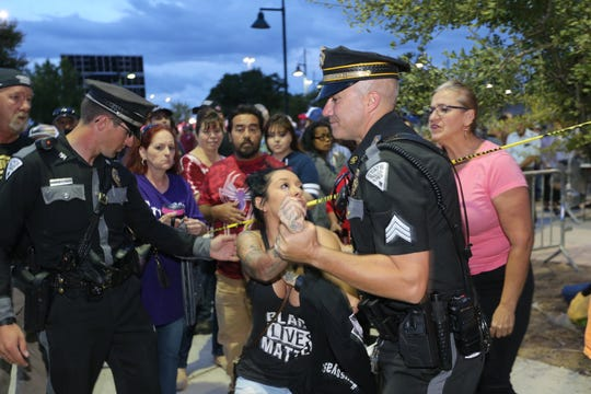 Río Rancho resident Jackie Montoya is detained by New Mexico State Police after an altercation with a Donald Trump supporter outside a Trump rally at the Santa Ana Star Center in Rio Rancho on Monday, Sept. 16, 2019.