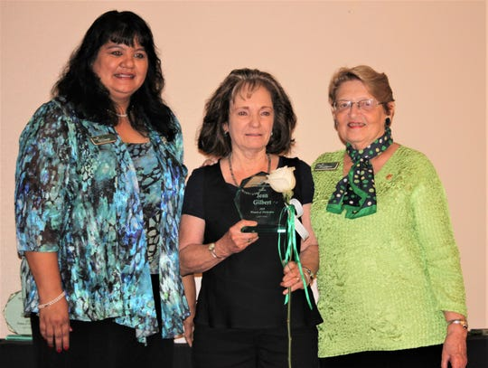 Jean Gilbert, center, holds her Woman of Distinction award on stage with Patty Craven, Chief Executive Officer for Troop 69546, left, and Judy LKeibrook, Board Chair, right.