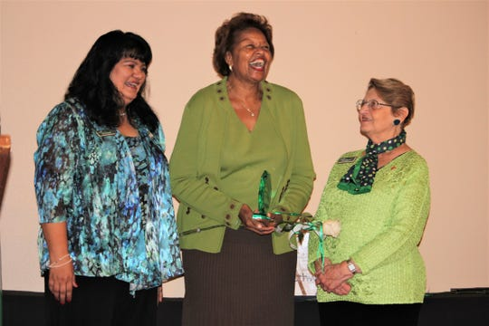 Julia Brown, center, holds her Woman of Distinction award on stage with Patty Craven, Chief Executive Officer for Troop 69546, left, and Judy Leibrook, Board Chair, right.
