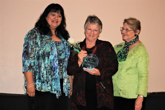 Kay Brilliant, center, holds her Woman of Distinction award on stage with Patty Craven, Chief Executive Officer for Troop 69546, left, and Judy Leibrook, Board Chair, right.