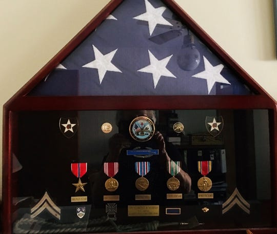 Myrold's son created this display of his medals which includes a Bronze Star. The rope with a medallion is a special medal awarded by the French government.