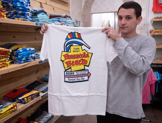 Sam Krossman, an employee of the Innerlight surf shop, shows off a shirt for sale at the company's downtown store emblazoned with the Pensacola Beach Sign logo.