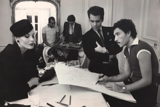 Fashion illustrator Antonio Lopez (r) sketches a model as designer Karl Lagerfeld (center) observes in the 1970s.