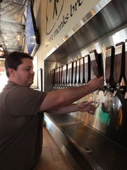 Head brewer Atruro Ruiz pours a pint at the Desert Monks Brewing Company tap room in Gilbert.