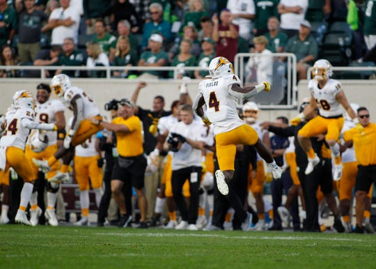 Arizona State players, including Evan Fields (4), celebrate at the conclusion of a win over Michigan State in an NCAA college football game, Saturday, Sept. 14, 2019, in East Lansing, Mich.