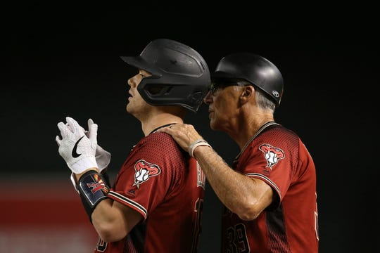 Arizona Diamondbacks' Carson Kelly, left, listens to Diamondbacks first base coach Dave McKay, right, as Kelly stands at first base during the third inning of a baseball game against the San Diego Padres Wednesday, Sept. 4, 2019, in Phoenix.