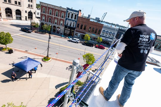 St. Clair County Sheriff Tim Donnellon looks down from the roof of the Michigan Mutual building in Port Huron during the annual Roof-Sit for Kids' Rooftop Rally Tuesday, Sept. 17, 2019, in downtown Port Huron.