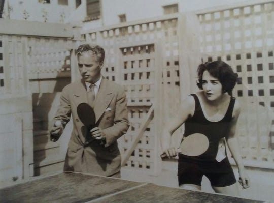 "Charlie Chaplin playing ping-pong in a formal suit, yet the unidentified woman is in swimwear. ""Must have been a pool party where he showed up after a business meeting and decided to play,"" said collector Jean Haines who owns the photograph."