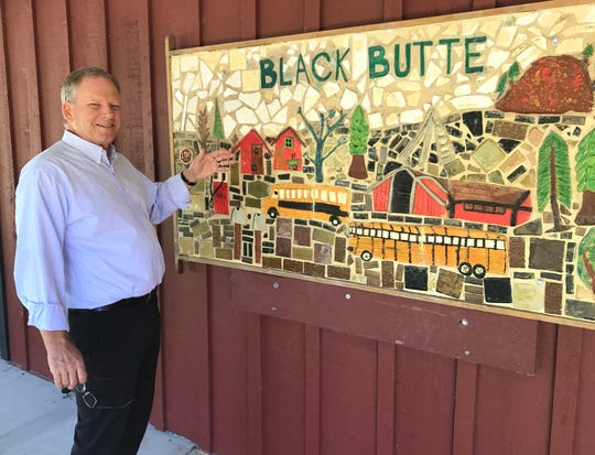 Don Aust, superintendent and principal for the Black Butte Union Elementary School District in Shingletown, stands next to a tiled mural at the elementary school.