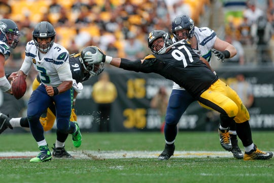 Seattle Seahawks quarterback Russell Wilson (3) scrambles away from Pittsburgh Steelers defensive end Cameron Heyward (97) on his way to a first down in the second half of an NFL football game, Sunday, Sept. 15, 2019, in Pittsburgh.
