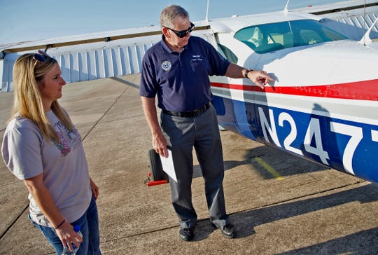 Kristin Gentry, left, listens to Terry Pricer as he performs a pre-flight check to a Civil Air Patrol aircraft Saturday, Sept. 14, 2019.