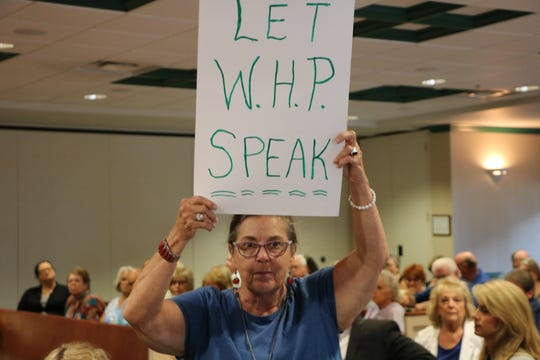 A woman holds a sign as the Worcester County Commissioners decided the fate of White Horse Park residents who can no longer stay in their homes year-round. White Horse Park is a campground subdivision in Berlin, which abuts Ocean Pines. The meeting took place Sept. 17, 2019.
