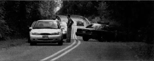 Maryland State Police investigate the Indiantown Road crime scene where Gregory Guy Collins was fatally shot on June 4, 2001.