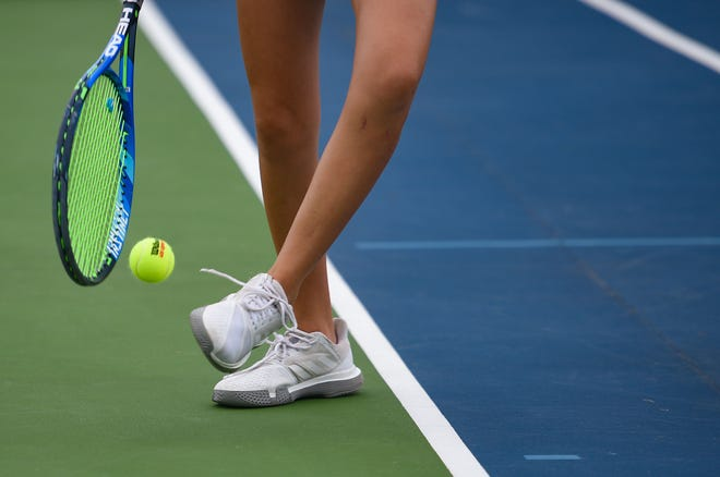 A tennis player kicks a tennis ball onto her racket before her serve on Monday, September 16.