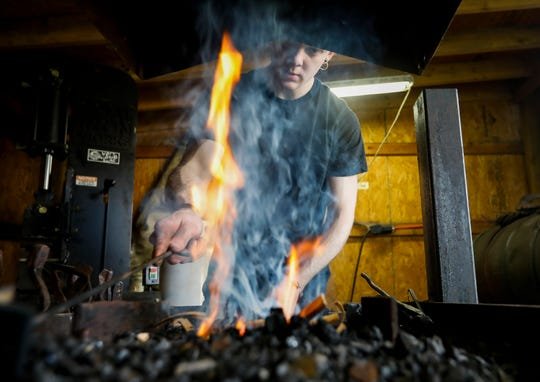 Collin Miller stokes the fire in his forge at his home in Brookline, Mo., on Monday, Sept. 16, 2019.
