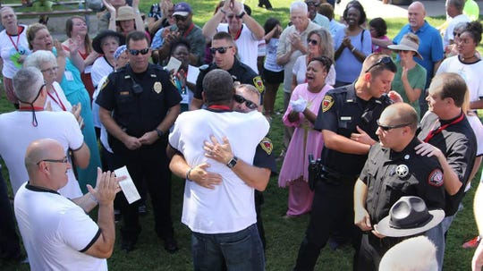 Pastor Steve Williams and Springfield Police Chief Paul Williams embrace after a prayer at the Unity on Division event in 2016.