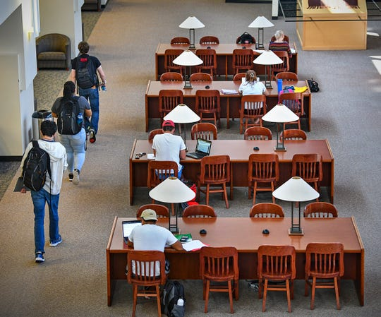 Students study at desks in the James W. Miller Learning Resources Center Tuesday, Sept. 17, 2019, at St. Cloud State University. The university announced Tuesday that four staff members at the library would be laid off at the end of this school year.