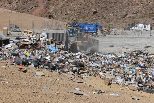 A truck rolls over trash at county landfill, compacting the material.