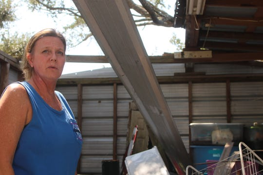Tonya Hewett stands in a damaged shed on her farm, recalling Hurricane Michael's destruction 11 months after the storm.