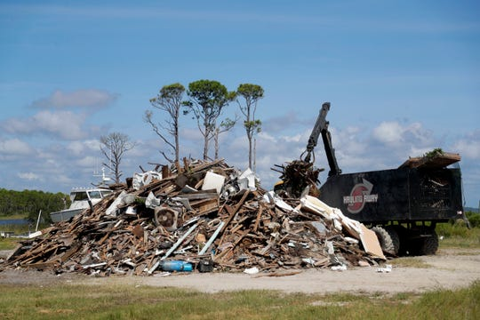 A debris removal truck empties just some of the debris picked up from along the sand roads on Dog Island. 11 months earlier Hurricane Michael tore through the island and the rest of the Panhandle leaving many without homes.