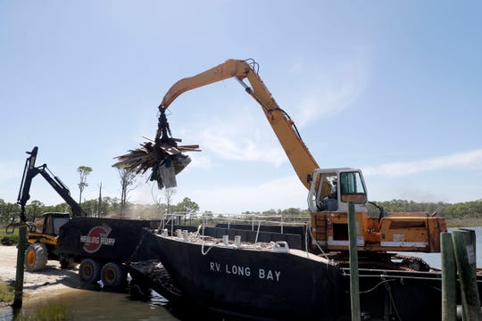 A large machine lifts debris from the back of a truck to put onto the barge to take back to the mainland from Dog Island. The debris is what was left behind in the path of Hurricane Michael in Oct. 2018.