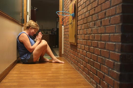 Tonya Hewett, 52, reenacts the day  Hurricane Michael hit, when she and her family sat in the brick-walled hallway of their Sneads home, praying for safety.