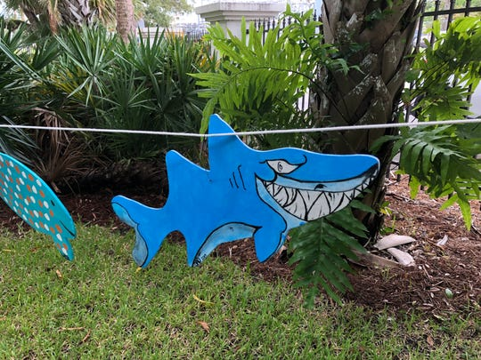 """Downtown galleries and businesses organized public painting parties during Art Walk for the """"Fish on the Fence"""" community project."""