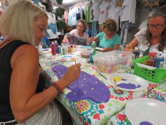 """Downtown galleries and businesses, including Notions & Potions, organized public painting parties during Art Walk for the """"Fish on the Fence"""" community project."""
