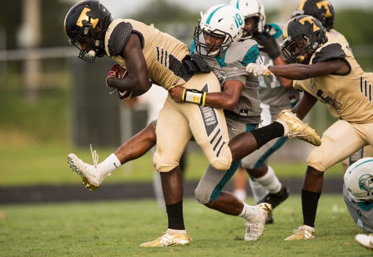 Treasure Coast's Joey Fleurjuste (left) runs the ball in for a touchdown as Jensen Beach's DaQuan Gonzales tries in vain to stop him in the first quarter of the high school football game Monday, Sept. 16, 2019, at Jensen Beach High School.