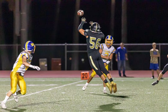 Oak Park High senior defensive end Luka Saric goes up for an interception during a game against Nordhoff earlier this season. The Eagles are unbeaten after four games.