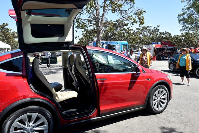 Guy and Victoria Hall, of Sacramento, stand back as they activate the demo mode on their 2016 Tesla X during the National Drive Electric Week event at the Ventura County Government Center on Tuesday. Demo mode synchronizes music with door movements and lighting activity on the car.