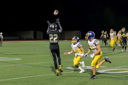 Oak Park High's Michael Holcomb makes a catch while being covered by two Nordhoff defenders during a game earlier this season. Holcomb is one of the senior leaders for the Eagles, who have started the season 4-0.