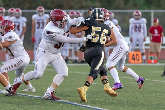 Luka Saric (56) rushes the passer during a game against Santa Paula earlier this season. The Oak Park defensive end has eight sacks in four games this season for the unbeaten Eagles.