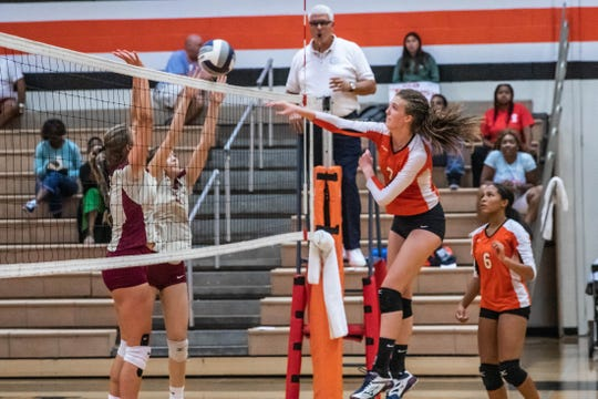 White Plains middle blocker Karleighana Jones swings at a ball during a match against Arlington.