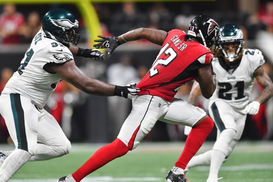 Atlanta Falcons wide receiver Mohamed Sanu (12) runs near Philadelphia Eagles defensive tackle Fletcher Cox (91) during the second half of an NFL football game, Sunday, Sept. 15, 2019, in Atlanta. (AP Photo/John Amis)