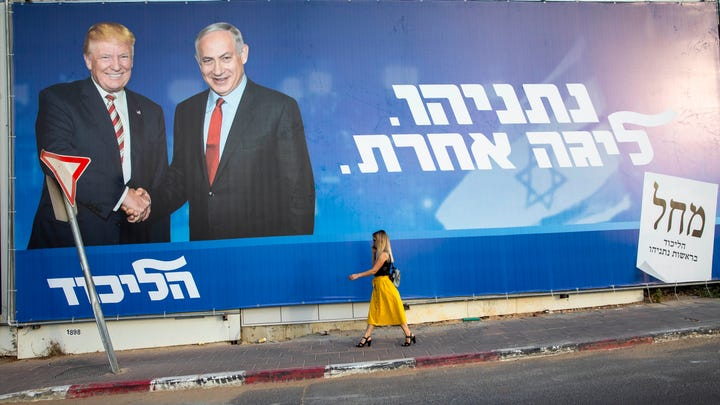 """An election campaign billboard for Israeli Prime Minister Benjamin Netanyahu, right, with President Donald Trump, in Tel Aviv, on Sept 15, 2019. In Hebrew, the billboard reads: """"Netanyahu, in another league."""""""