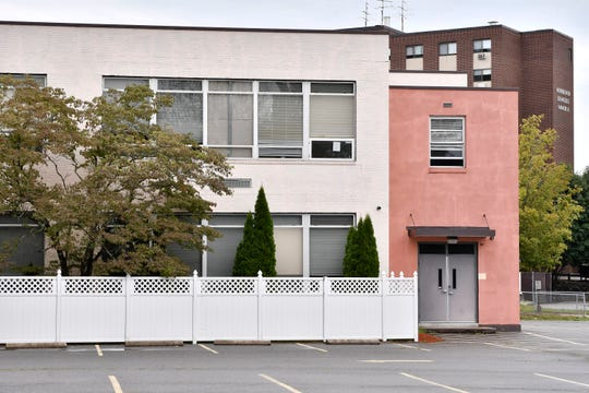 The former Sacred Heart elementary school stands in front of apartment buildings named for Monsignor Deangelis in West Warwick, Rhode Island, which was operated by the neighboring Sacred Heart Church in the 1960s.