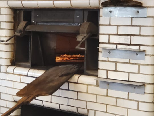 Pizzas cook inside the coal-burning oven, the same way pizzas have been made at Pepe's for 94 years.