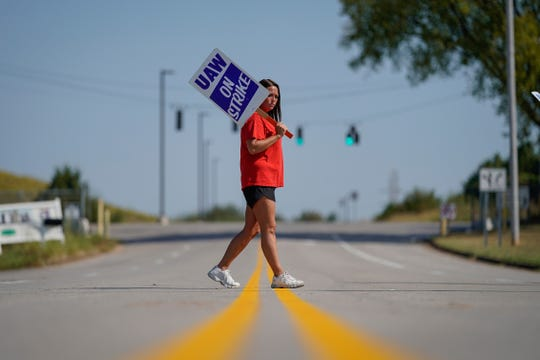 Temporary plant worker Shanuel Merevith, of Edmonson County, Ky., carries a sign and walks the picket line outside the General Motors assembly plant in Bowling Green, Ky, Sept. 16, 2019.