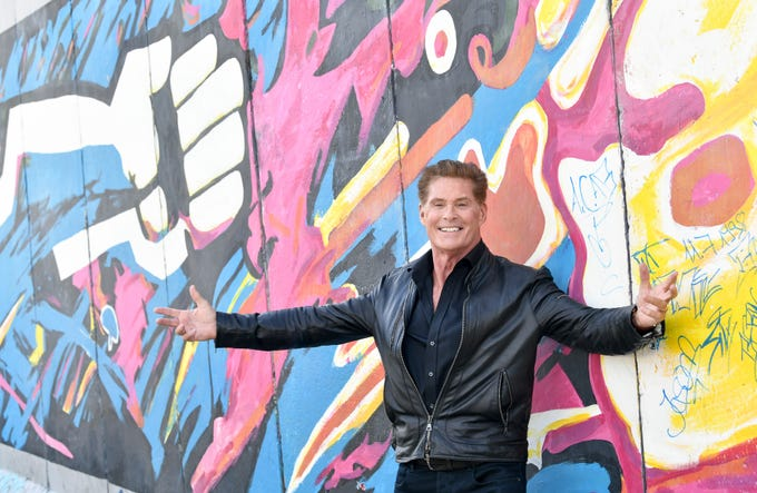 """David Hasselhoff poses for media during a presentation event for his audio book """"Up against the Wall - Mission Mauerfall' in front of a painting of the East Side Gallery, a part of the former Berlin Wall, in Berlin on Sept. 17, 2019."""