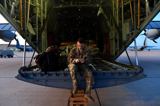 Senior Airman Brian Cann sends a text to the other airmen in his C-130 crew in the early morning before members of the 317th Air Wing at Dyess Air Force Base deployed to Africa and Afghanistan on Sept. 9. This was the first full deployment of the 39th Airlift Squadron in more than a decade.