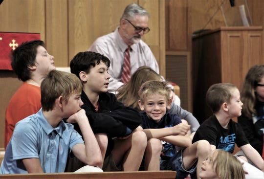While youngsters wiggle through kids' church Sunday, the Rev. Scott Seymour contemplates what his preaching later in the service.