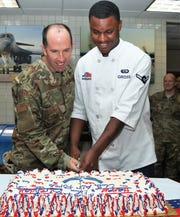 Col Matthew Newell, left, 7th Bomb Wing vice commander and highest ranking airman in the room, cuts the birthday cake Wednesday with the lowest ranking airman, an Air Force tradition.