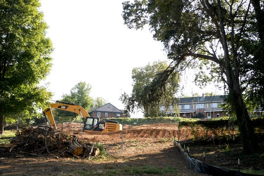 A pile of cut trees and limbs sits outside the construction fence as work stops for the day on the Lee Walker Heights public housing neighborhood in downtown Asheville's South Slope on Sept. 17, 2019. Lee Walker Heights, the city's oldest housing development, is being transformed into a mixed income, mixed-use neighborhood, the plan for which involves clear cutting the surrounding trees to lower the hill the neighborhood sits on.