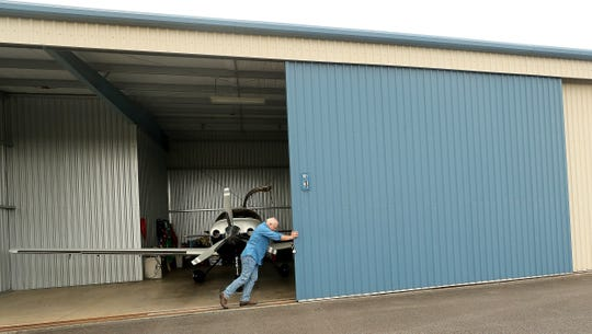 Pilot Harry Anderson pushes open his hangar door at Bremerton National Airport on Wednesday.