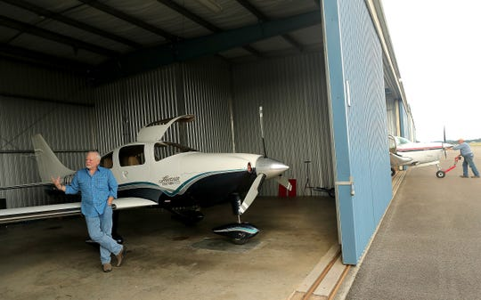Pilot Harry Anderson leans against his plane inside the hangar at the Bremerton National Airport while talking about his completion of a second solo flight around the globe on Wednesday.