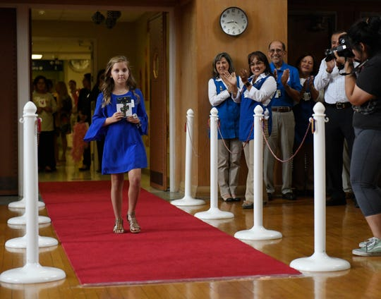 Eight-year-old Lucy Webb walks down the red carpet, Wednesday, Sept. 18, 2019. There were over 30 entries for the contest. The hospital has had the holiday cards for 27 years.