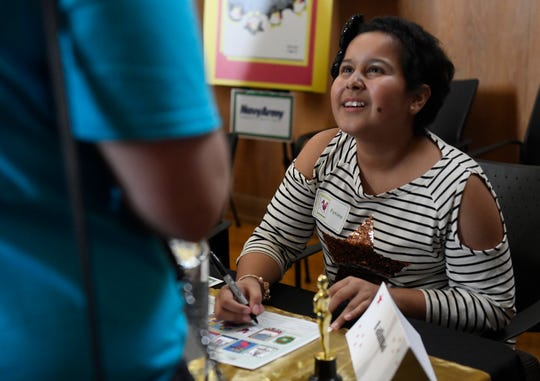 Twelve-year-old Fatima Herrera signs an autograph, Wednesday, Sept. 18, 2019. Herrera, from Pharr, Texas, designed a pink flamingo with Christmas lights on it.
