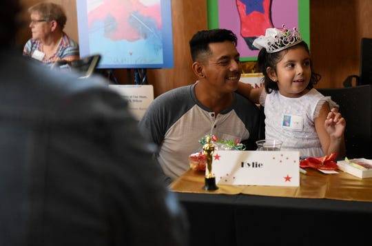 Julio Oviedo Morales, left, hugs his seven-year-old daughter Kylie Gonzales Wednesday, Sept. 18, 2019. Gonzales designed a red boot.